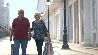 Old male and female walking in city streets with shopping bags - lifestyle concept