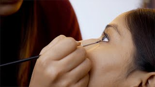 Makeup artist applying eyeliner on the eyes of a young lady using a cosmetic brush
