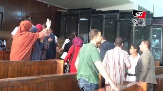 أهالي متهمي «مذبحة كرداسة» يلوحون بشارات رابعة لذويهم من خلف القفص