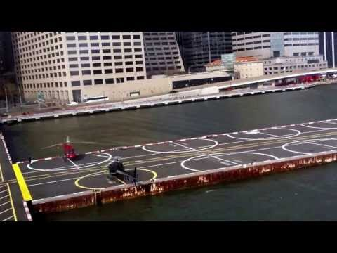 Helicopter landing in New York City port. Brooklyn Bridge in background.