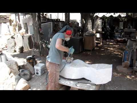 Sculptress Dey Young carving a torso at Art City Studios