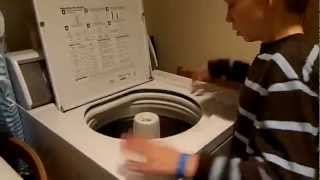 Парень играет на стиральной машине как на барабане.