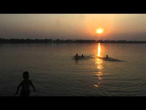 Kids take a bath a long  Mekong River with Sun set