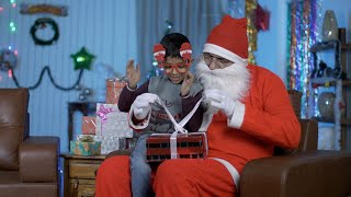 Old Santa and smiling Indian boy opens a Christmas present during Christmas season