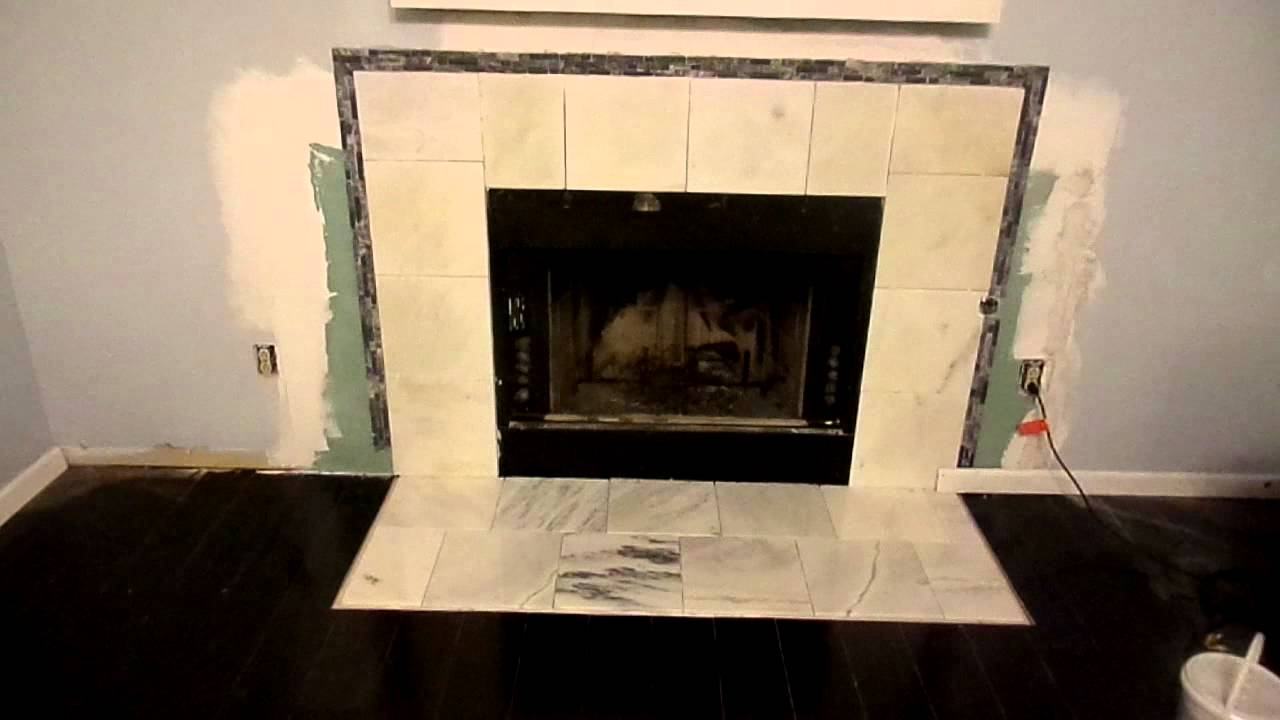 Shows the first part of a placing white marble outlined with a black and gray glass tile.