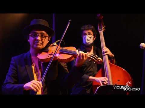 Show ao vivo, violinista solista de camiseta amarela blazer preto e chapéu preto. Os três músicos q os acompanham estão usando máscara no rosto e o baterista protegido por paredes de acrílico. No cenário, violinos pendurados.