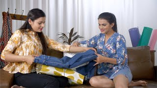 Beautiful Indian girl showing new clothes to her friend in a living room