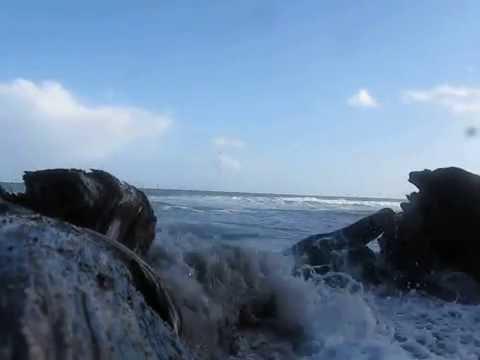 Rolling waves push onto sandy beach.