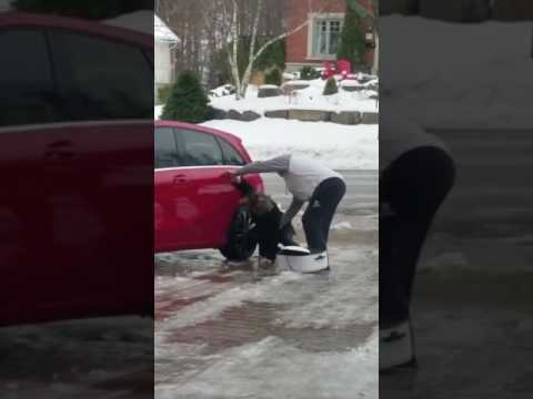 woman trying to get in her car while slipping on ice