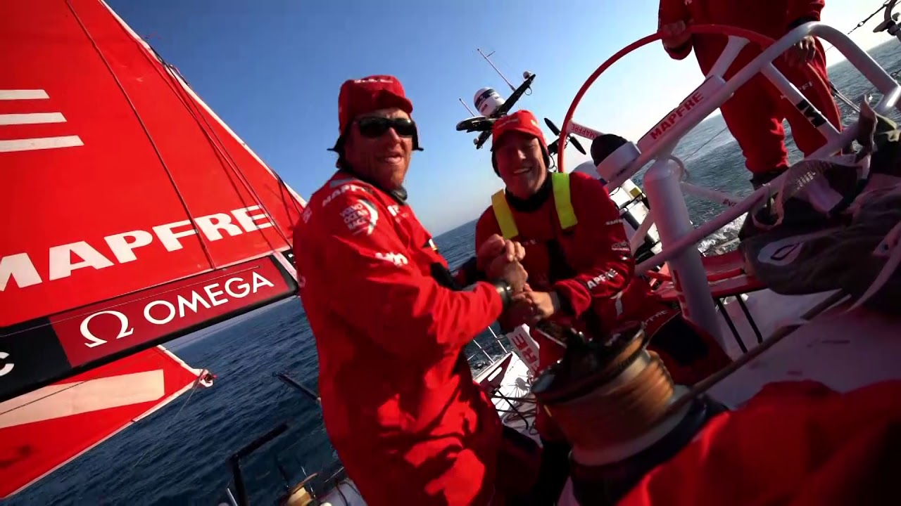 Pablo talks in Spanish on the weather rail as MAPFRE sails upwind in 10 knots of wind on port. Sounds like he's talking about the competition, the tricky last part of the race. Repeats in English: Finish in Cardiff will be quite tricky for all the boats. A lot of work to windward; we have some chances. We want Dongfeng to be as far back as possible, but it's not something we can control. Have to be fast and do the best we can and wait and see. A little over 100 miles to go. 30 miles to Vestas, so quite a lot of distance. Stacking. Grinding in the runner. Dolphins alongside. Slomo dolphines. Pablo, Joan, and Rob at the nav station looking at a sched. They discuss with Neti in the cockpit. Brunel still leading? Just. Rob: I'm just happy that Dongfeng look less likely to win the leg. Sunset. Drone shots of MAPFRE sailing upwind under MH0 and J3. Such beautiful peaceful shots. Low-altitude drone.