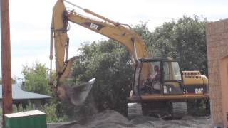 CAT 315C Excavator working multiple construction sites digging dirt and loading dump trucks