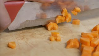 Woman chopping carrots into small pieces
