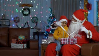 Cute little kid in Santa hat opening colorful gift box with Santa Claus - Christmas time