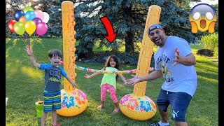 Sally play Inflatable Limbo game with water balloons - Family fun time