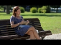 Young Girl Sitting At The Bench In a Park And | Stock Footage - Videohive