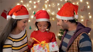 Happy Indian Family on Christmas - Cute little girl hugging her parents and opening gift