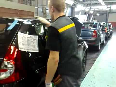 Car assembly worker makes final tweaks to the doors