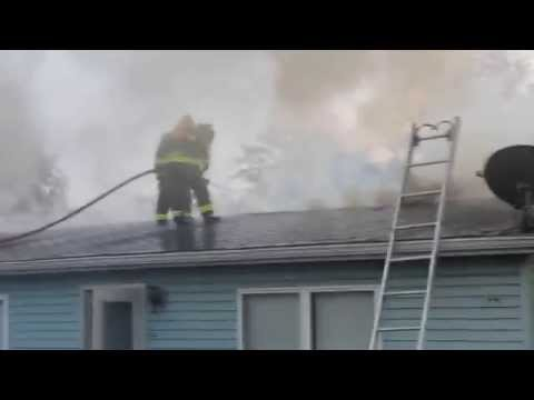 Raw video: Firefighter struggles with hose on roof