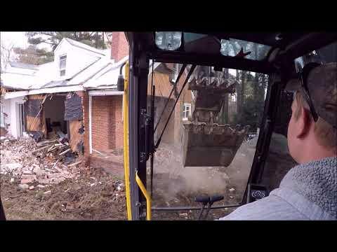 Excavator Removing Bricks Off A House