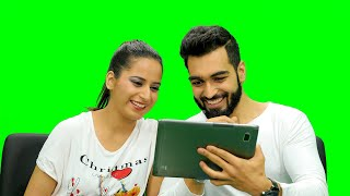 Mid shot of a couple sitting on chair and watching something funny on a tablet against the green screen