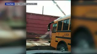 Train narrowly misses school bus stopped under railroad crossing arm