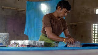 Block Printing - A man adjusting the blue cloth for block printing