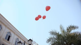 A young beautiful female releases red heart balloons in the sky - Valentine's day