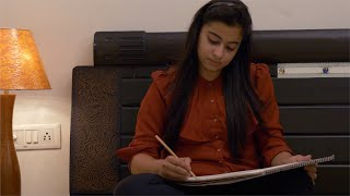 Creative young Indian girl drawing her next designs for exhibition
