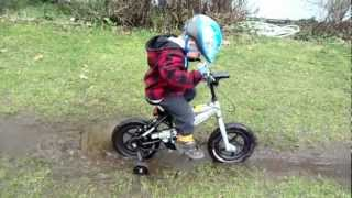 Boy gets bike stuck in deep mud hole.