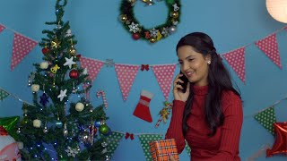 Beautiful young woman busy greeting her friends on a call on Christmas Eve