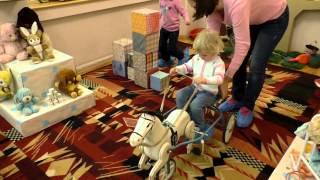 Діти грають з іграшками СРСР: конячкою, дитячим посудом, ляльками і т. д. Виставка радянських іграшок.