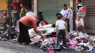 مواطنون يبحثون عن ملابس في بقايا حريق المحلات التجارية بـ«حارة اليهود»