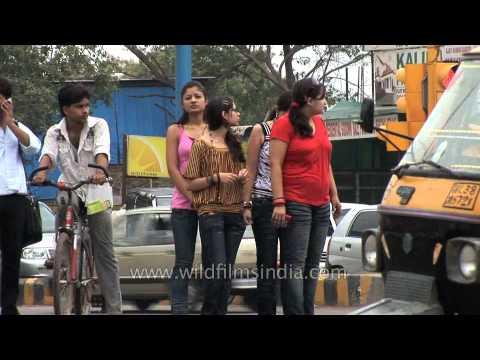 Modern Indian girls cross street while speaking on the mobile, Faridabad
