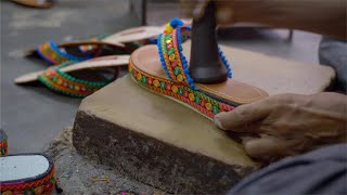 Professional local craftsman beating the soul of the sandal using a tool to paste it well