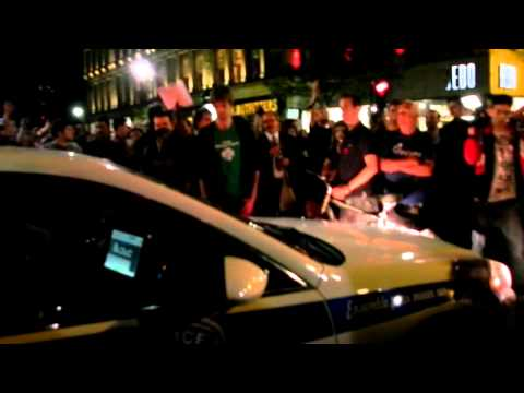 Protesters block access to a police car