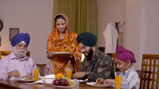 Indian Punjabi lady in ethnic wear serving food to her family with love - Army man with his father, son, and wife