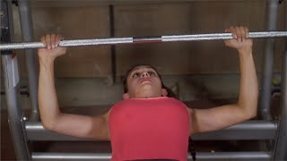 Active young woman athlete doing bench press with the barbell in gym