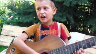 маленький мальчик играет на гитаре