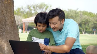 Cute little kid learning how to work on a laptop from his dad - technology invasion