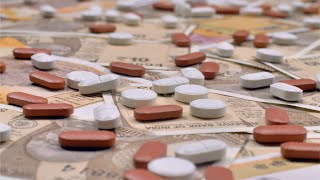 Pan shot of pills lying on table with Indian currency notes