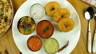 Moving shot of beautifully plated South Indian food placed on a wooden platform
