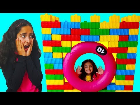 Esma play with toy colored bricks made a playhouse