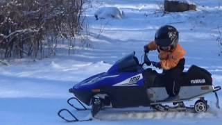 Four-year-old riding snowmobile Yamaha 120 SRX