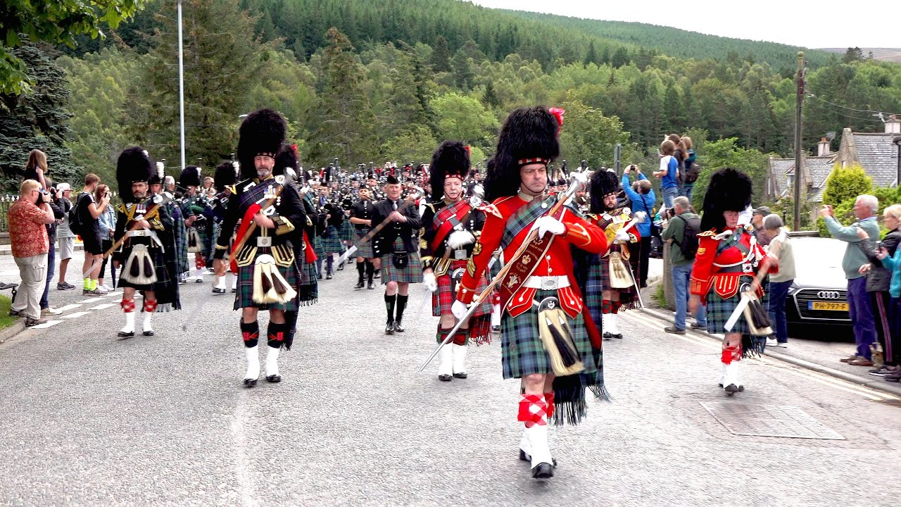 Download Massed pipes & drums parade through town to the 2019 Ballater Highland Games in Scotland