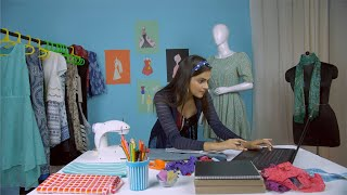 Attractive Indian fashion designer working in her self owned fashion studio