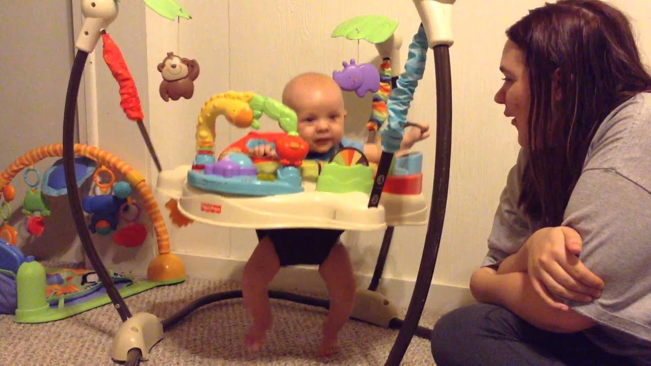 4 month old baby boy playing in his bouncer and talking to momma