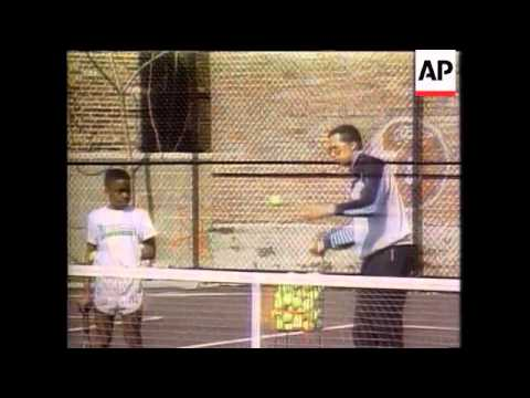 Arthur Ashe coaching black youths on tennis court:
