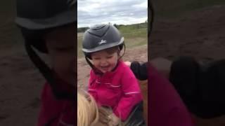 Little girl laughs on horse ride