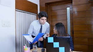 Young female boss working on laptop while her subordinate gives information from the file