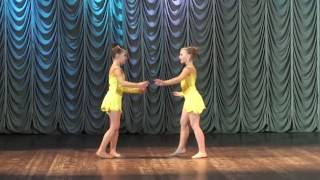 Танцуют дети. Две очаровательных девочки танцуют на сцене